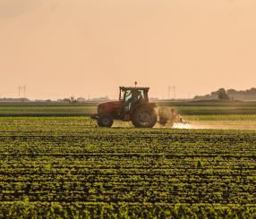 Farmer Driving Tractor In A Crop Field - Commercial Loans